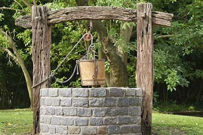 Stone well with a bucket on a rope.